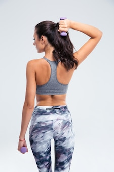 Back view portrait of a fitness woman working out with small dumbbells isolated on a white wall