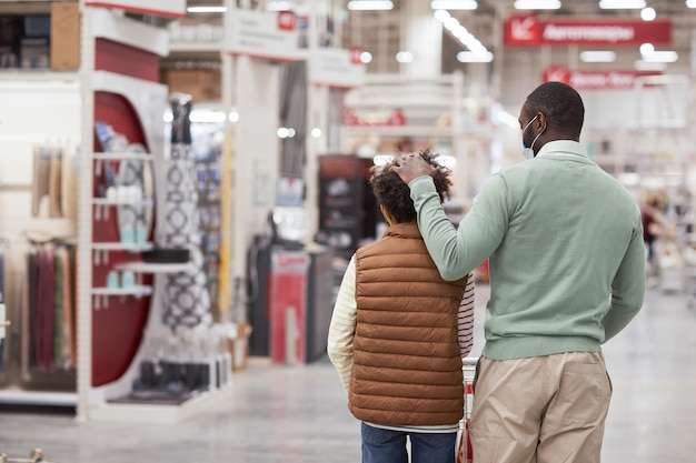Back view portrait of loving african-american father ruffling hair of son while shopping together in supermarket, copy space