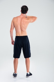Back view portrait of a man standing with neck pain isolated