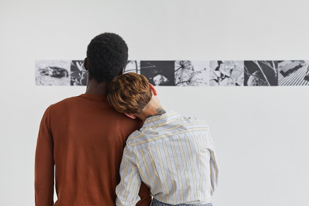 Back view portrait of mixed-race couple embracing while looking at paintings at modern art gallery exhibition,