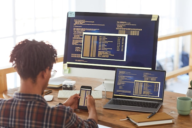 Back view portrait of modern african-american man holding smartphone with code on screen while working at desk in office, it developer concept, copy space