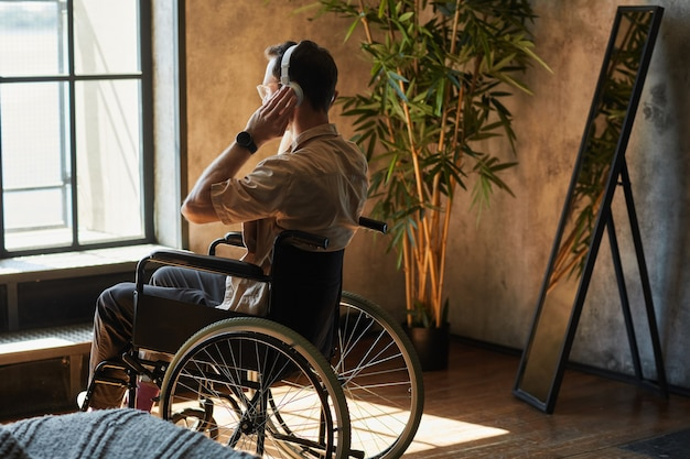 Back view portrait of modern disabled man in wheelchair listening to music at home, copy space