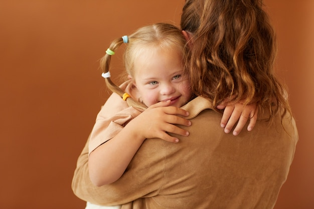 Back view portrait of mother holding happy daughter with down syndrome while standing against plain brown surface in studio