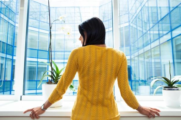 Вид сзади портрет деловой женщины, стоящей в офисе возле окна