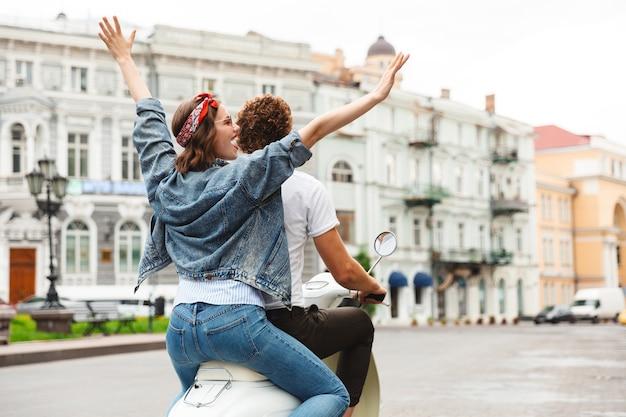 街の通りで一緒にバイクに乗って幸せな若いカップルの背面図の肖像画