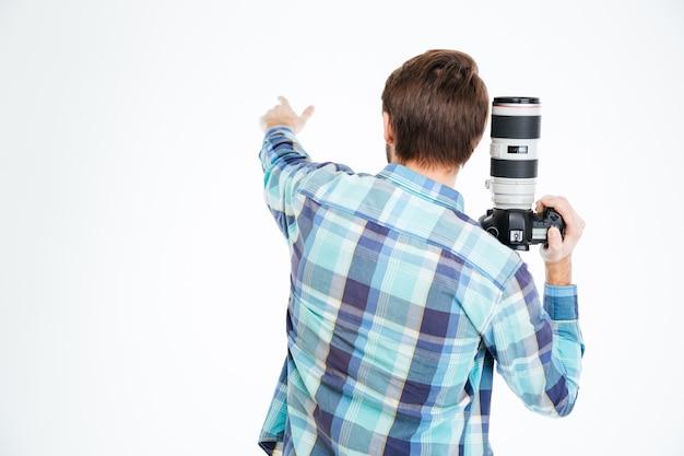 사진 카메라를 들고 뭔가 흰색 배경에 고립 가리키는 남성 사진 작가의 다시보기 초상화