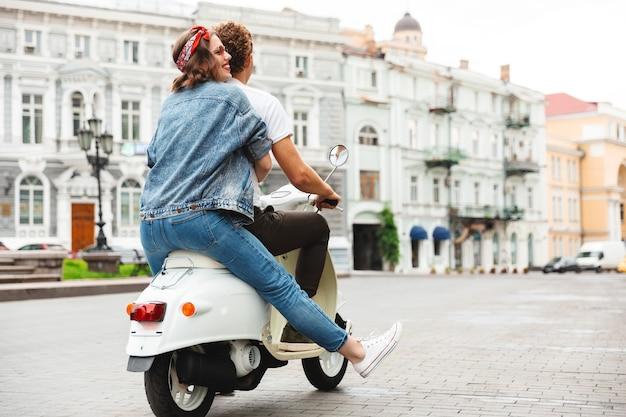 街の通りで一緒にバイクに乗っている現代の若いカップルの背面図の肖像画