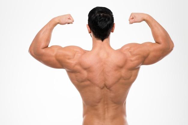 Вид сзади портрет мускулистого мужчины, стоящего изолированно на белой стене