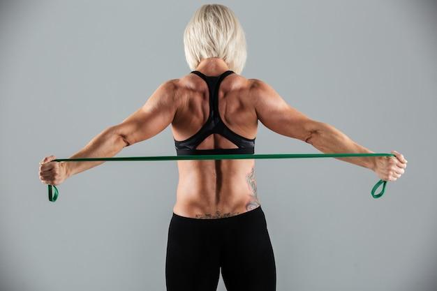 強い筋肉の大人のスポーツウーマンの背面図の肖像画