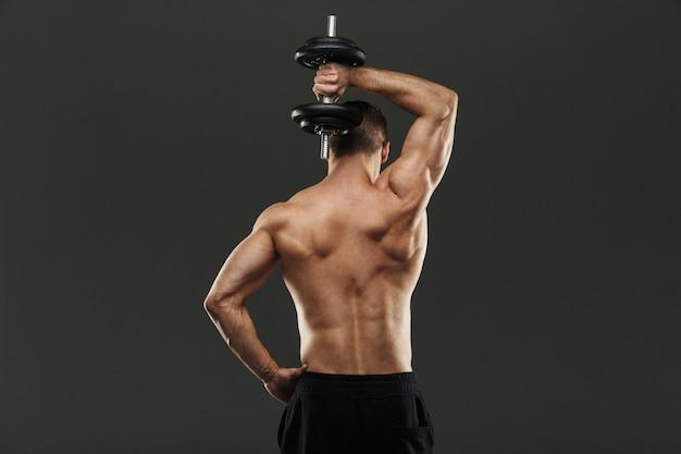 Задний портрет сильного мускулистого спортсмена без рубашки