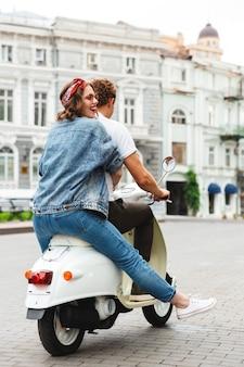 街の通りで一緒にバイクに乗ってスタイリッシュな若いカップルの背面図の肖像画