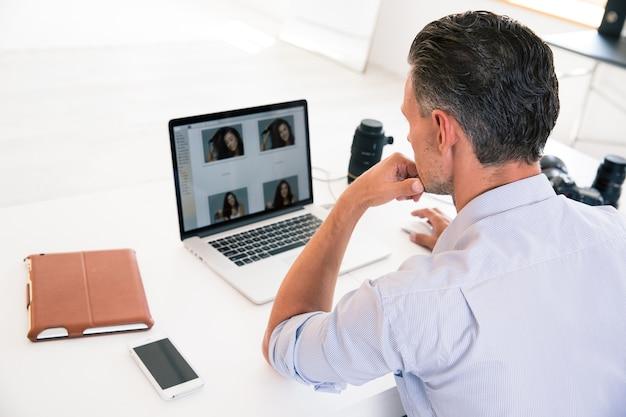 그의 직장에서 노트북을 사용하는 젊은 남자의 다시보기 초상화