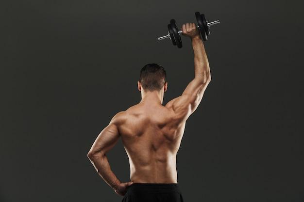 Задний портрет молодого мускулистого спортсмена без рубашки