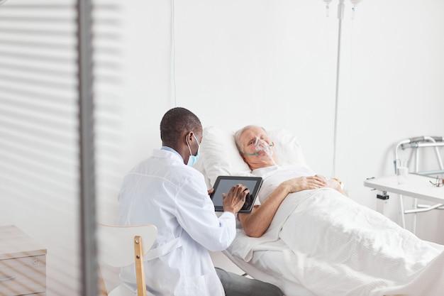 Вид сзади портрет афро-американского врача, использующего цифровой планшет, сидя у пожилого пациента на больничной койке, копией пространства