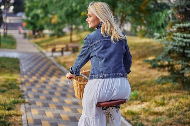 녹색 도시 공원에서 자전거를 타는 아름다운 금발 백인 여성의 뒷모습 초상화