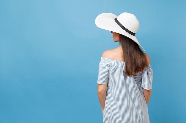 白い夏の大きな広いつばの日よけ帽のエレガントなファッションの若い女性の背面図の肖像画、ドレスは頭に手を置き、青いパステルカラーの背景で隔離のコピースペースを脇に見てください。ライフスタイルのコンセプト。