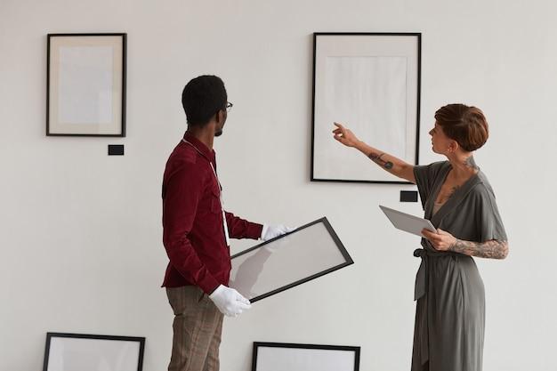 Вид сзади портрет женщины-менеджера художественной галереи, инструктирующей работника, вешающего рамы для картин на белой стене, во время планирования выставки в музее,
