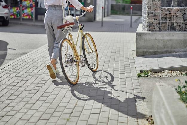 거리에서 복고풍 도시 자전거와 함께 걷는 회색 바지를 입은 여성의 뒷모습 초상화