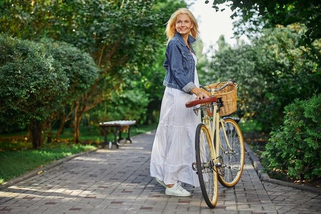 녹색 공원을 걷고 있는 흰 드레스를 입고 행복한 미소를 짓고 있는 여성의 뒷모습 초상화