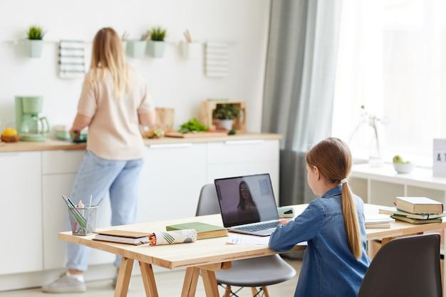 バックグラウンドで母親と一緒に居心地の良いキッチンのインテリアの机に座っている間、家庭教師または教師とオンラインクラス中にラップトップを使用して小さな女の子の背面図の肖像画、コピースペース