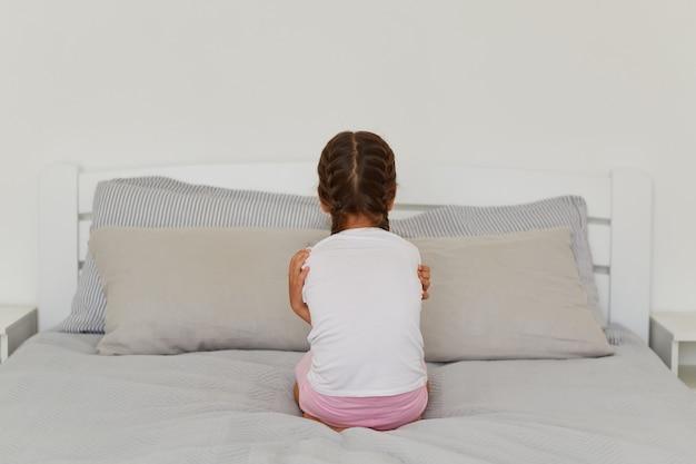 검은 머리와 땋은 머리를 가진 어린 소녀의 뒷모습 초상화는 카메라에 거꾸로 앉아 있고, 기분이 상하고, 방에서 혼자 포즈를 취하는 등 누구와도 이야기하기를 원하지 않습니다.