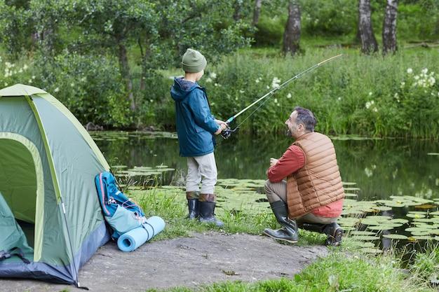 Вид сзади портрет зрелого отца, учит сына рыбалке во время совместного похода на озеро, копией пространства