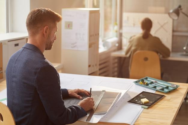 엔지니어 사무실에서 책상에서 작업하는 동안 청사진과 계획을 그리는 성숙한 남자의 다시보기 초상화,
