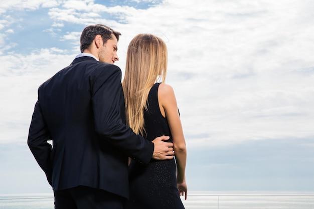 屋外で抱き締めて海を見ているロマンチックなカップルの背面図の肖像画