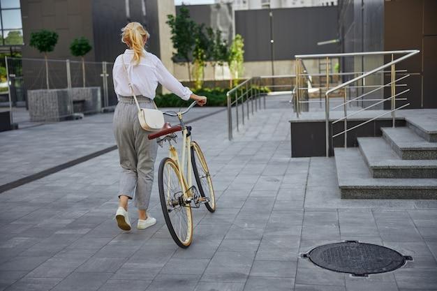 현대적인 자전거로 도시를 걷는 세련된 성인 유럽 여성의 뒷모습 초상화