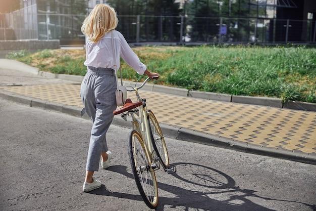 햇살이 비치는 날 도시 거리를 걷고 있는 복고풍 도시 자전거를 탄 여성 관광객의 뒷모습