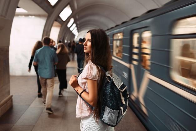 Вид сзади портрет молодой девушки с рюкзаком в ожидании поезда в метро.