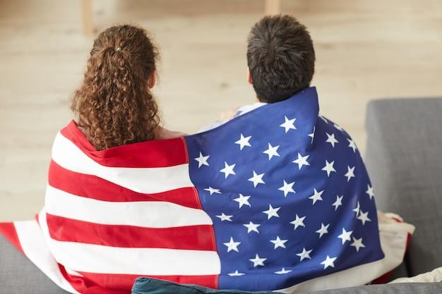 Вид сзади портрет молодой патриотической пары, держащей американский флаг во время просмотра телевизора дома