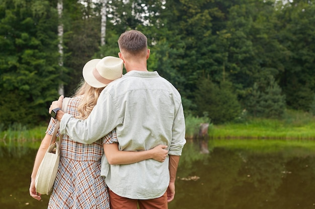 Back view portrait of romantic adult couple embracing while posing by lake in rustic countryside scenery
