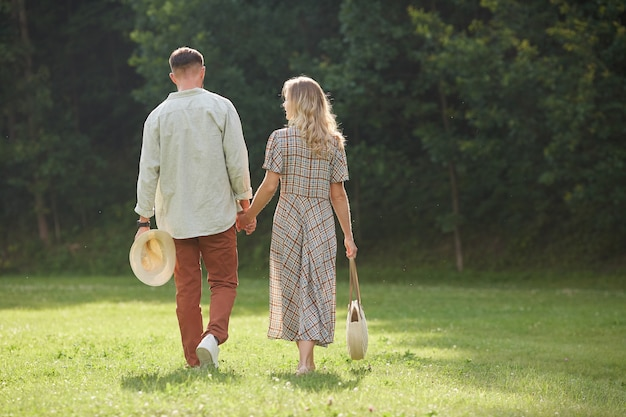Back view portrait of romantic adult couple holding hands while walking on green grass in nature scenery