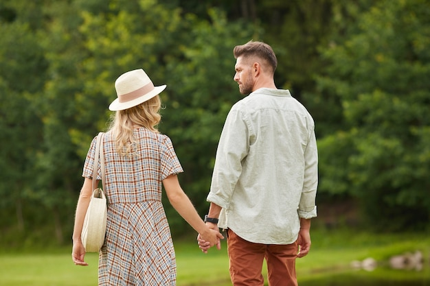 Back view portrait of romantic adult couple holding hands while walking towards river in rustic countryside scenery