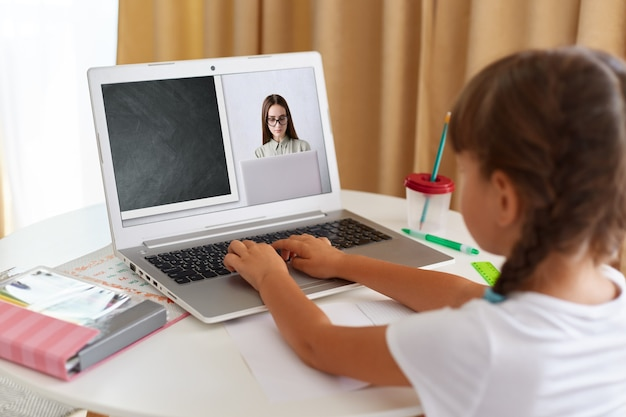Back view portrait of schoolgirl wearing white t shirt sitting in front of laptop and looking at screen, having online lesson via web camera, distant education.