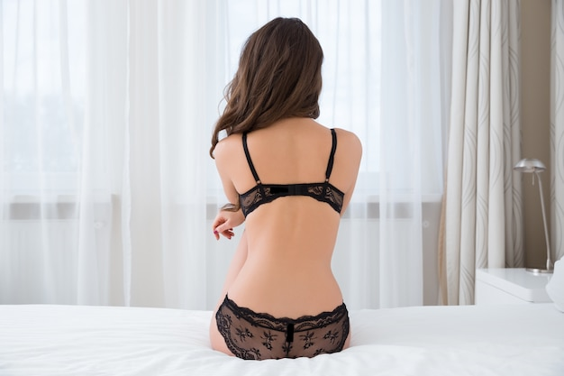 Back view portrait of a sexy woman in lingerie sitting on the bed