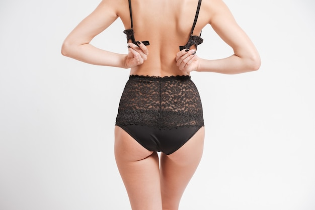 Back view portrait of a sexy young woman unbuttoning her bra isolated