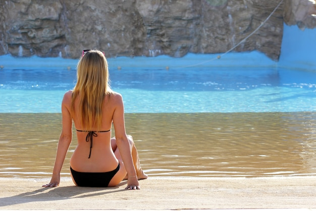 Back view portrait of a single woman watching on a water pool