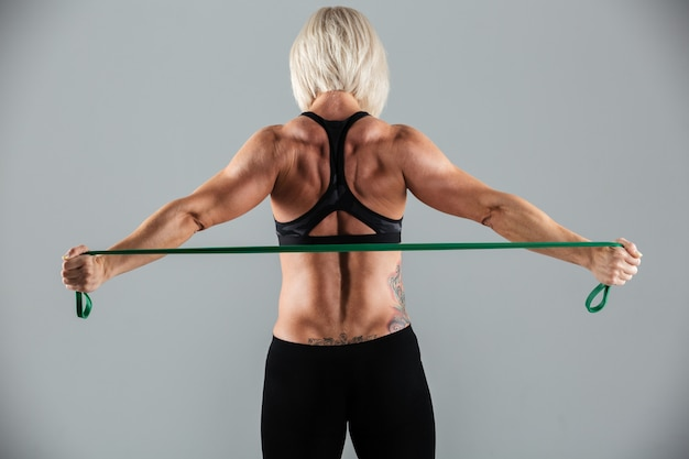 Back view portrait of a strong muscular adult sportswoman