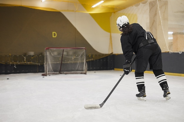 Back view portrait of unrecognizable hockey player leading pluck during practice on ice