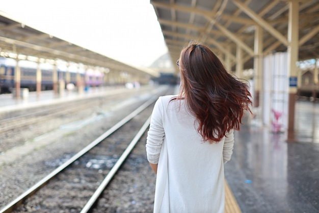 Back view portrait of young asian woman standing while waiting in train station