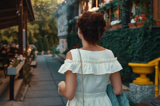 通りを歩いて背面図肖像若い都市女性