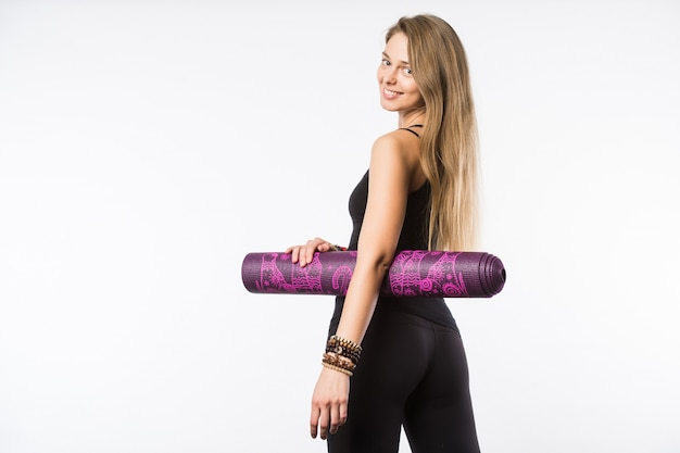 Back view portrait of a young fitness woman with yoga mat