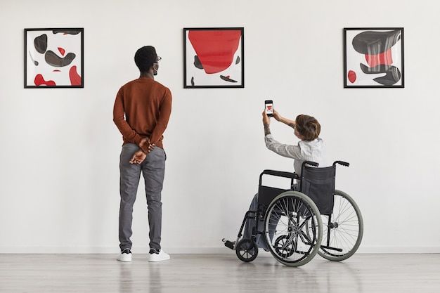 Back view portrait of young woman using wheelchair taking photo of artwork while visiting accessible museum,
