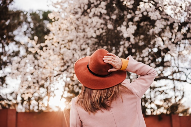 Back view portrait of young woman wearing modern hat at sunset in park. beautiful almond tree flowers background. springtime and blossom