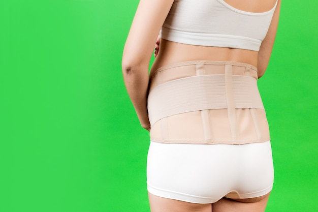 Back view of pregnant woman in underwear wearing pregnancy bandage at green background with copy space. close up of orthopedic abdominal support belt concept