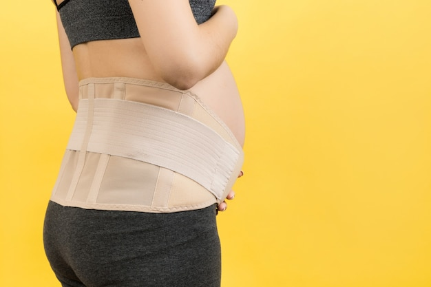 Back view of pregnant woman wearing pregnancy belt at yellow background with copy space