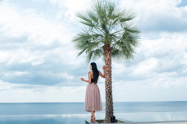 背面図:コスモポリタンカクテルを飲みながら、ヤシの木と完璧な海の景色を望むインフィニティプールの近くに立ってリラックスした長い白いドレスを着たきれいな女性。エキゾチックな休日、休暇を旅行します。