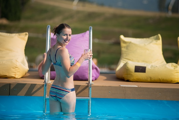 Back view pretty woman going out of the pool, turned around and smiling, holding a glass of drink